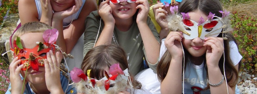 Children wearing paper masks decorated with natural materials