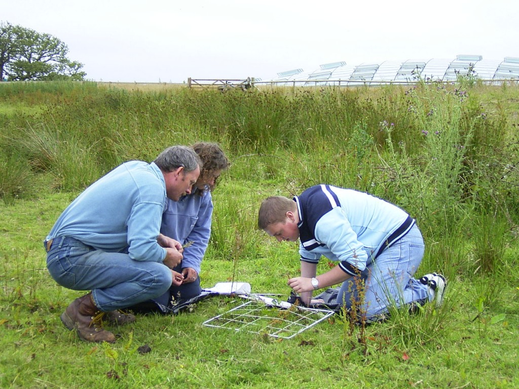 Two students study a quadrat in the grass on the National Nature Reserve with their teacher.