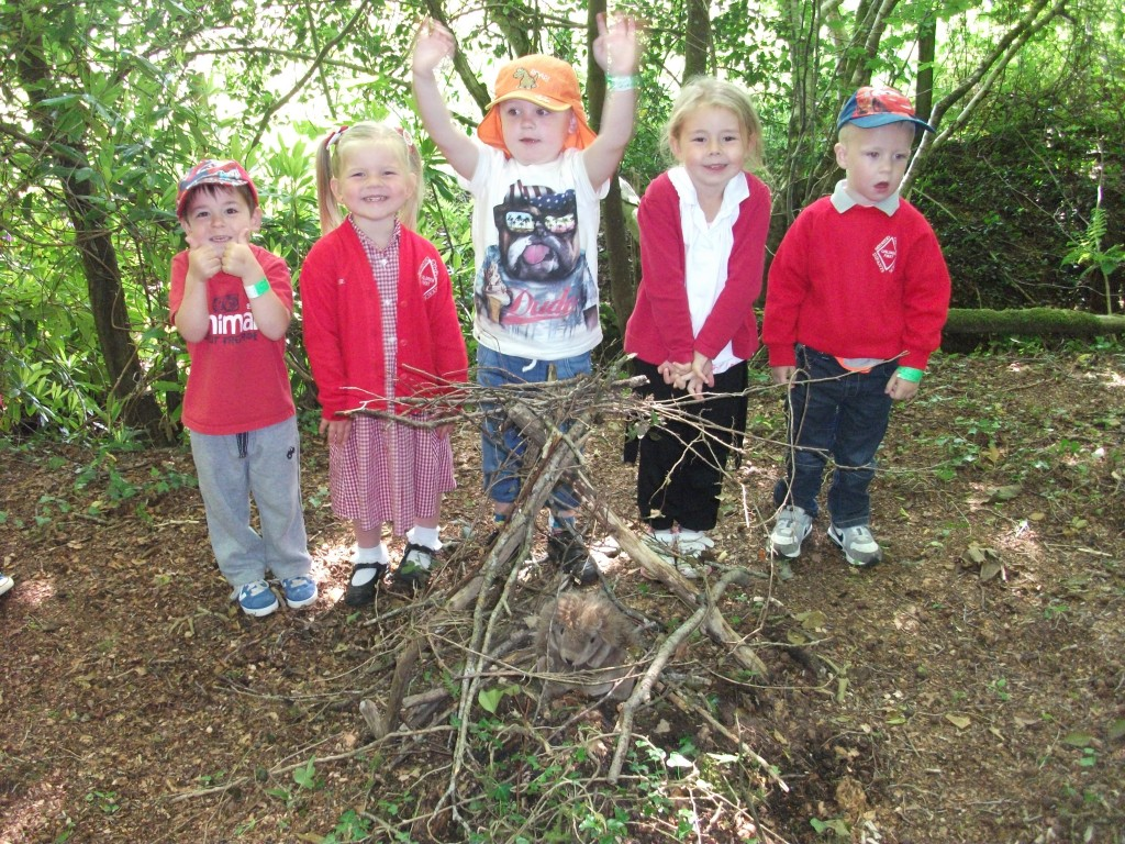 5 children surrounding the shelter they have built using sticks