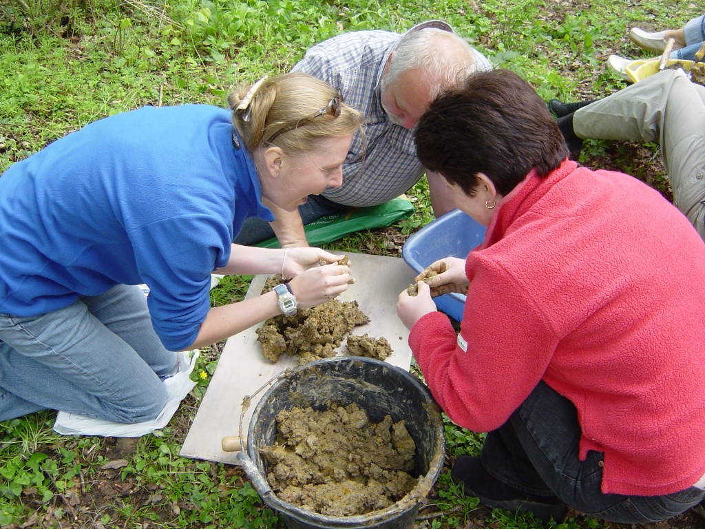 Three teachers kneeling in the grass, smiling as they roll natural clay in their hands.