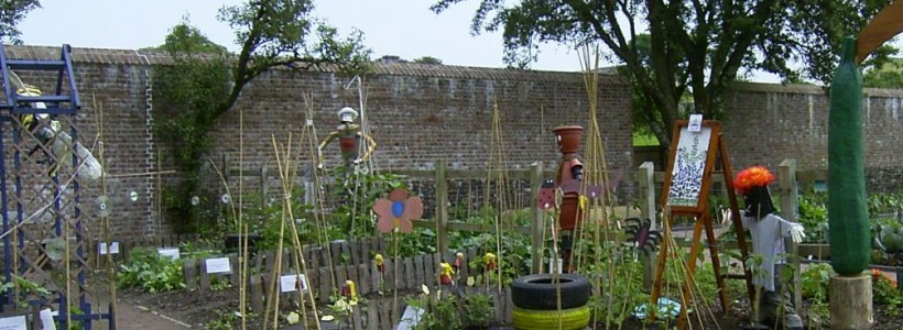 A shot of a school garden with a path through the middle, things growing in tires, bean poles supporting plants and homemade scarecrows.