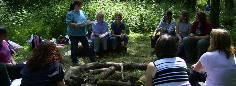 A group of teachers sit on logs around a fire pit while one teacher shares her ideas with the group.