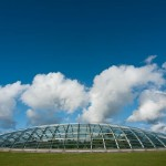 Lovely picture of the Great Glasshouse with very green grass below and a very blue sky above.