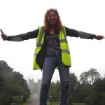 Picture of a smiley lady with shoulder length curly hair in a high-vis vest standing on top of a willow sculpture